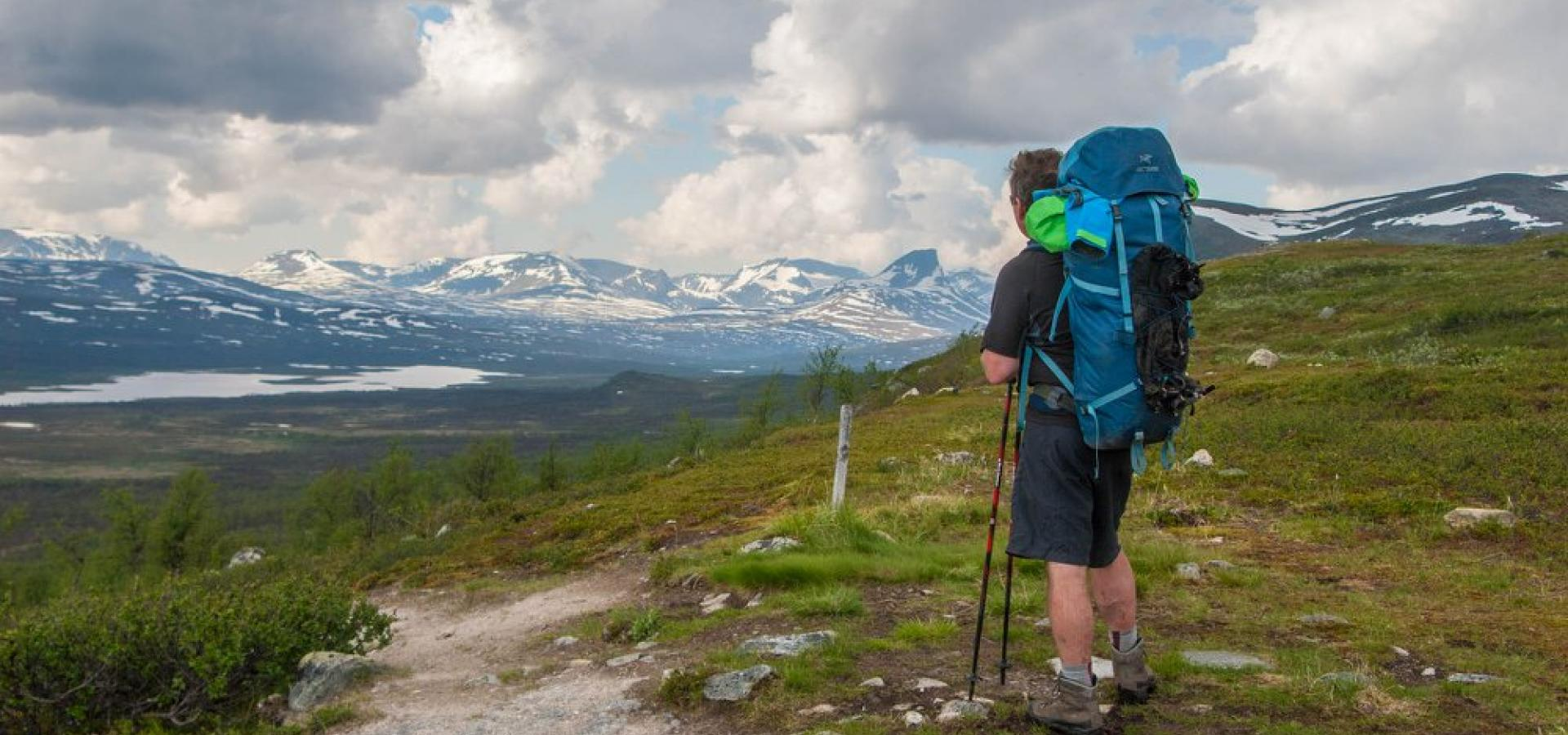 Hiker with a big blue backpack standing by a path and looking towards the snowcapped mountains in the distance