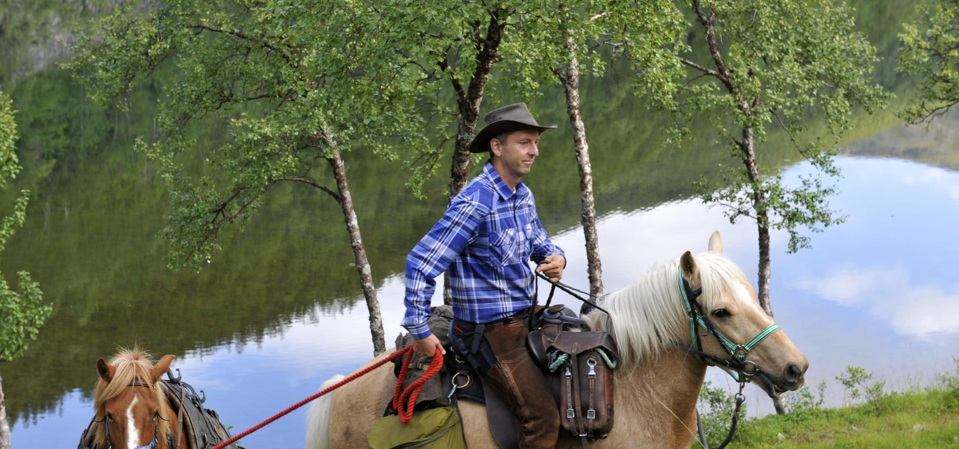 Riding a Lyngen horse by the river, a pack horse following