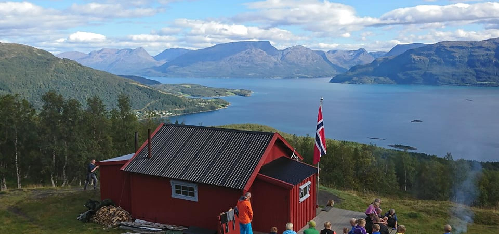 Red cabin in the mountains with views towards the fjord and mountains