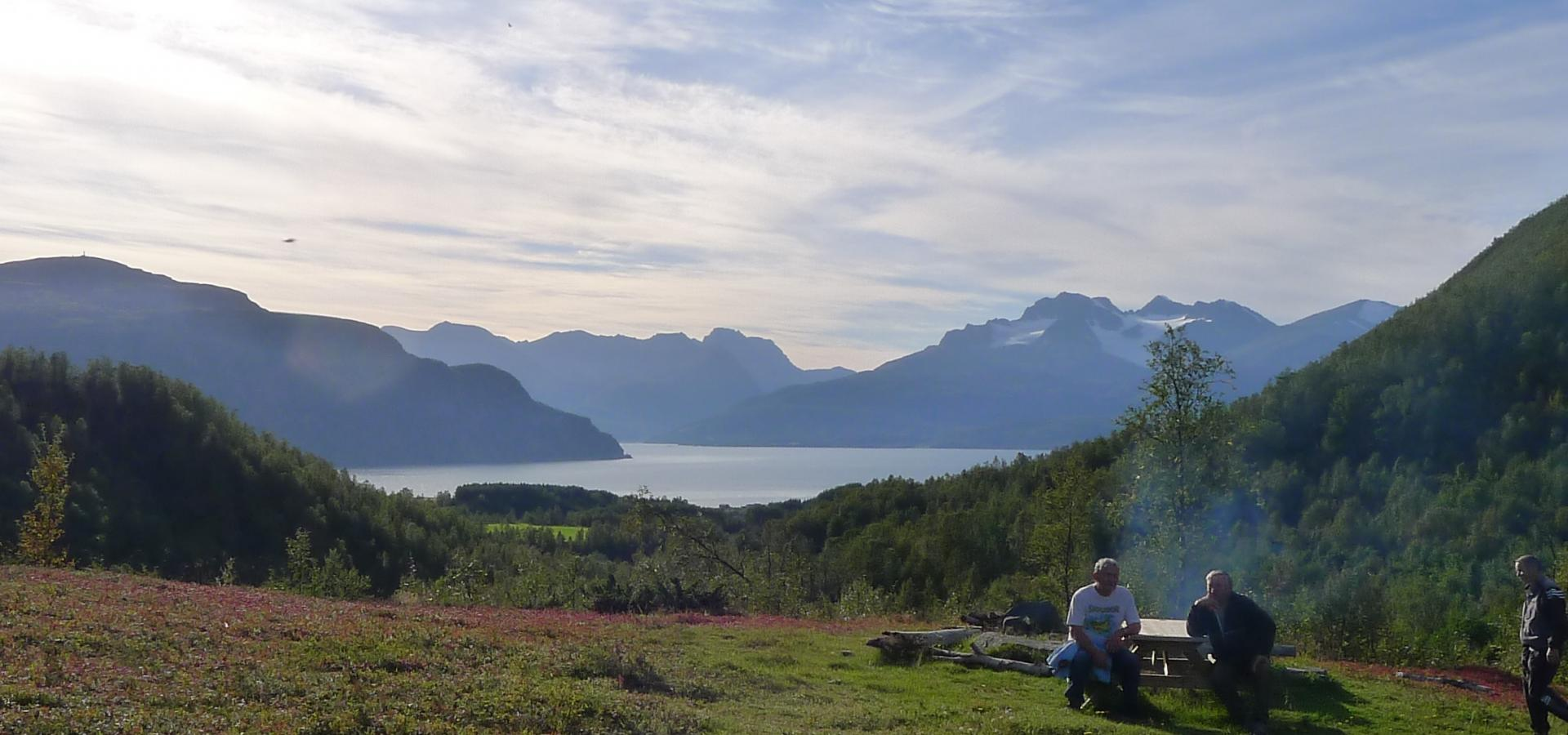 Two persons sitting on a outdoor table, in the background the fjord and the mountains