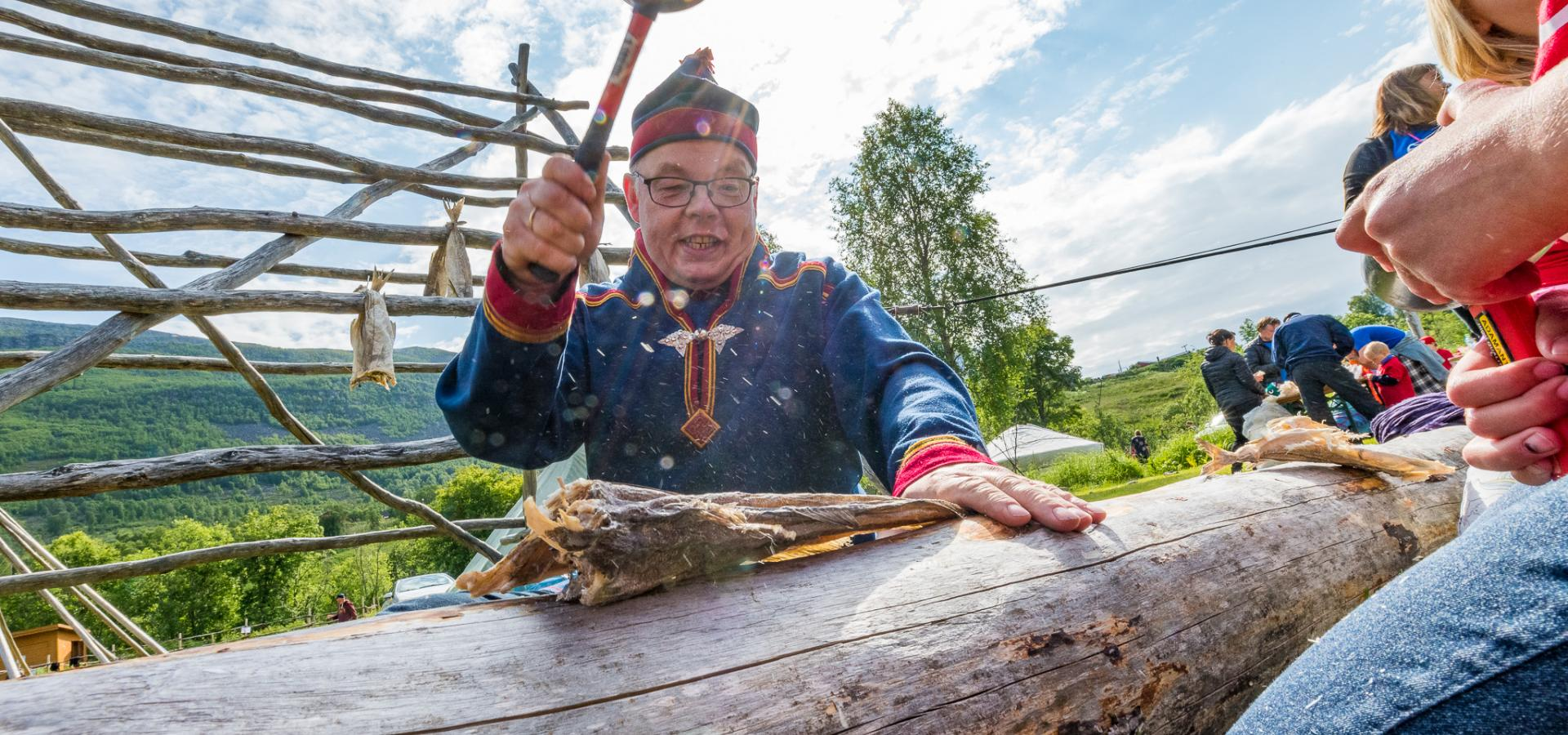 Hammering dried fish, wearing a sami suit