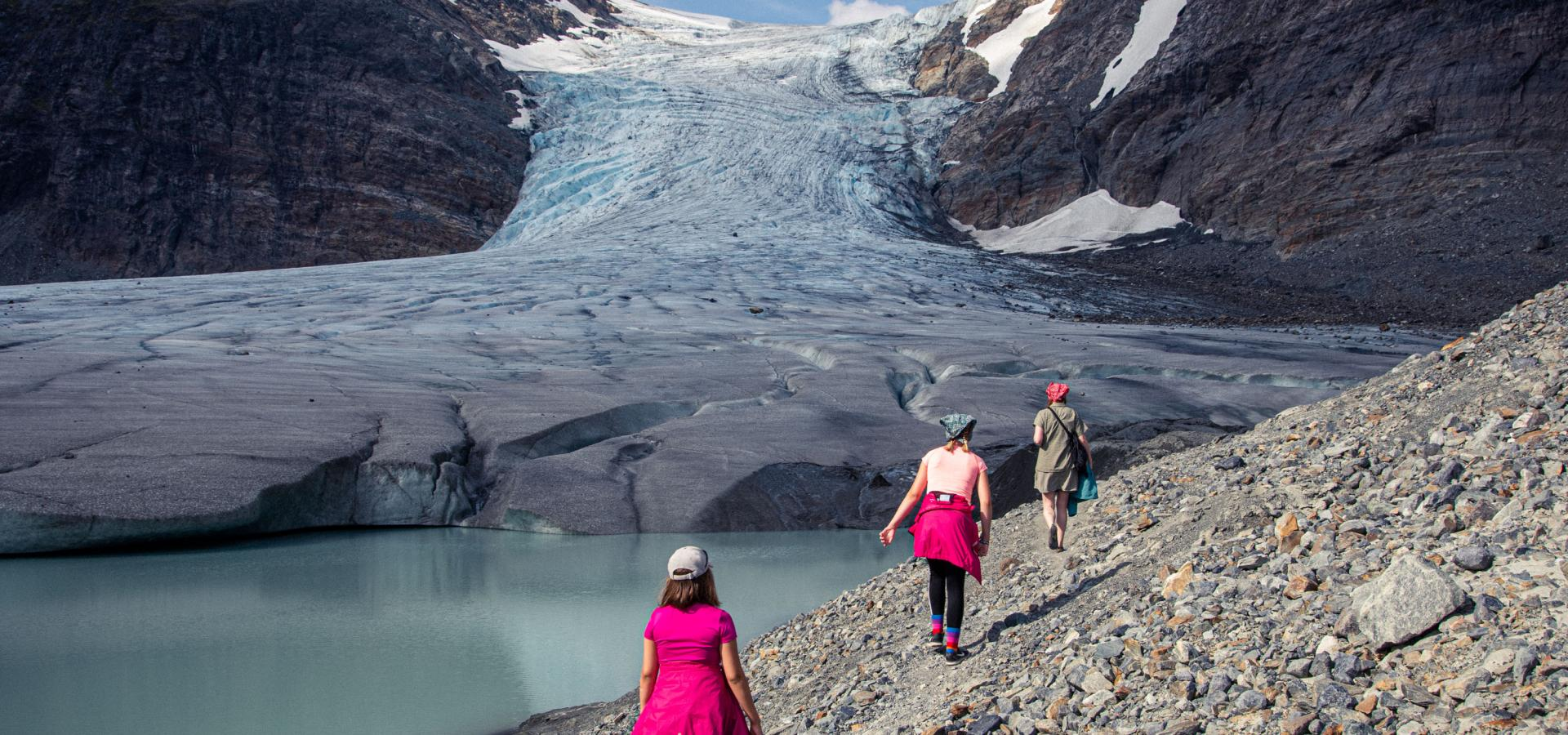 3 persons walking towards the glacier on a rocky ground