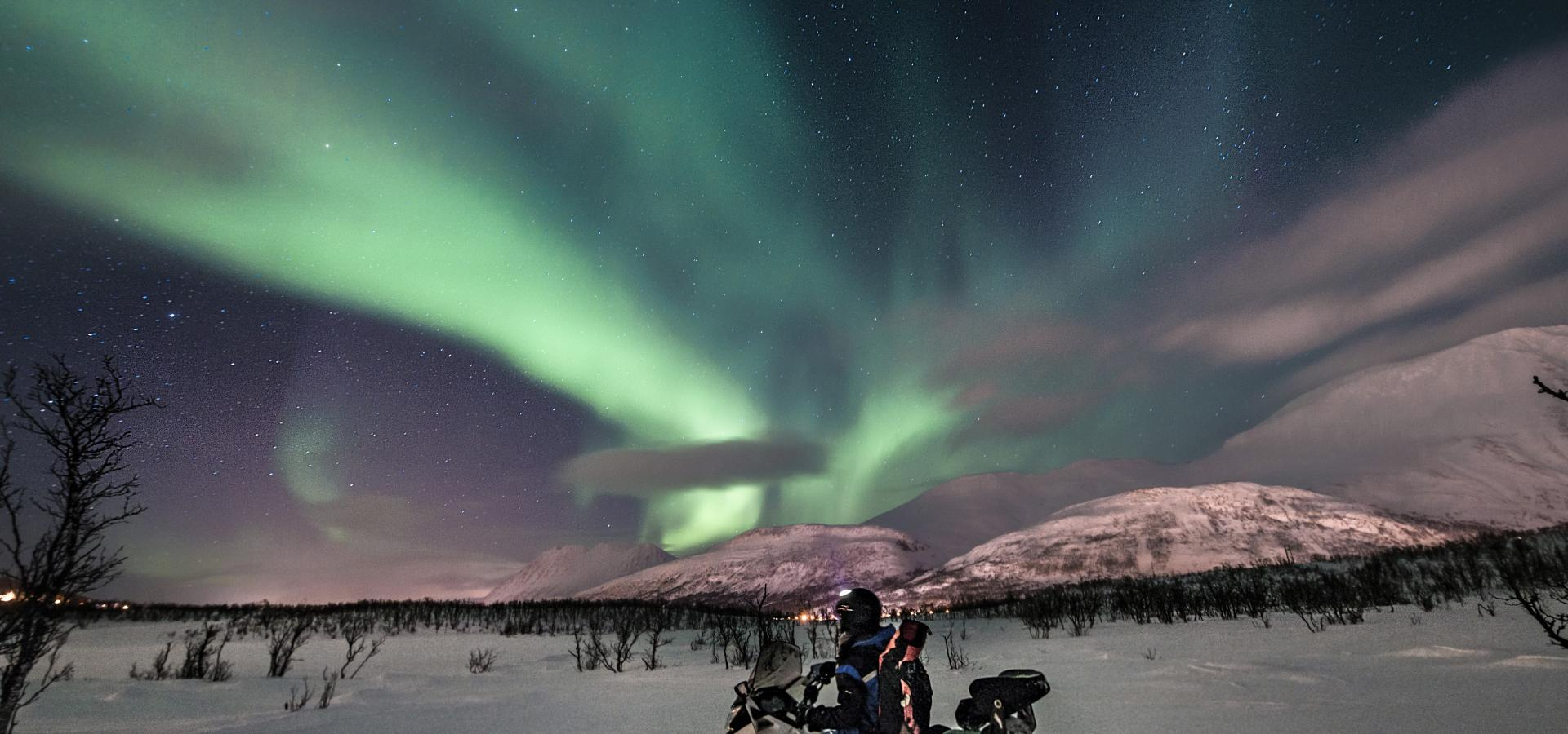 Snowmobiling under the northern lights in the Lyngen Alps, Northern Norway