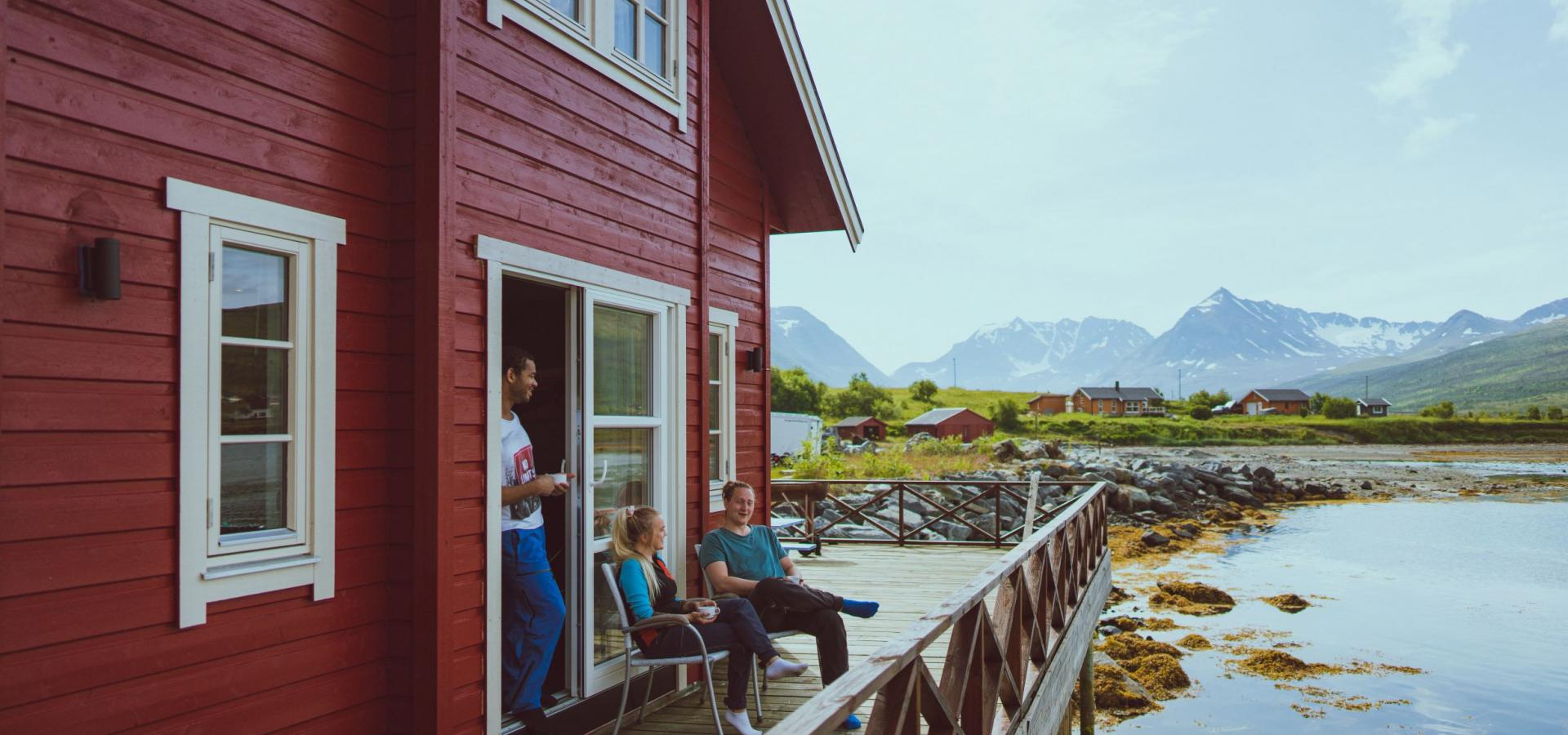 A red cabin by the fjord and 3 persons enjoying life outside on the pier, mountains in the background