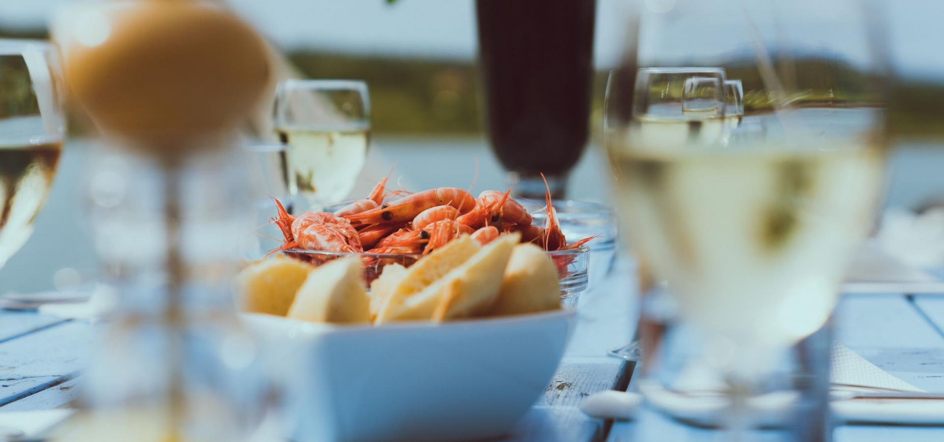 A summer table with glasses of wine, bowls with with bread and shrimps