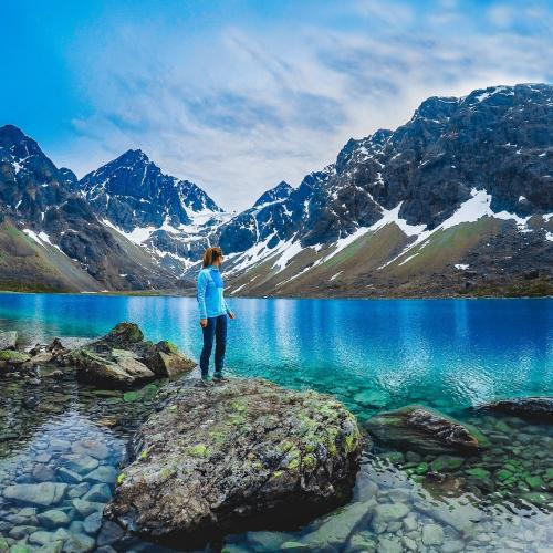 Standing by the Blue lake, enjoying the view of the lake and the Lyngen Alps