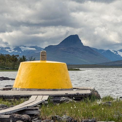 The yellow painted border marker at the three country cairn with the lake and norwegian mountains in the background
