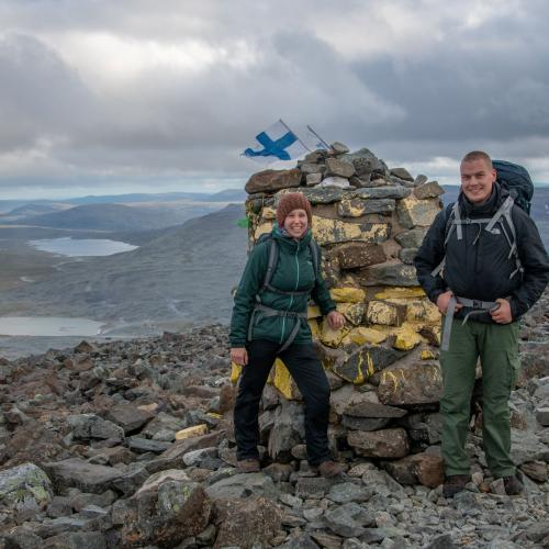 Two hikers by the cairn at Halti, with a view towards some lakes