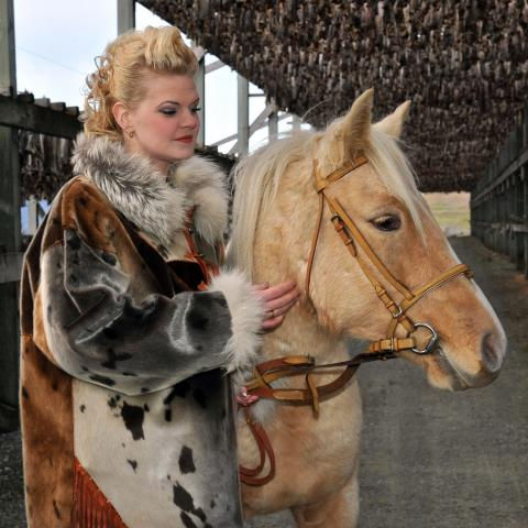 A woman dressed in a fur coat, together with her horse