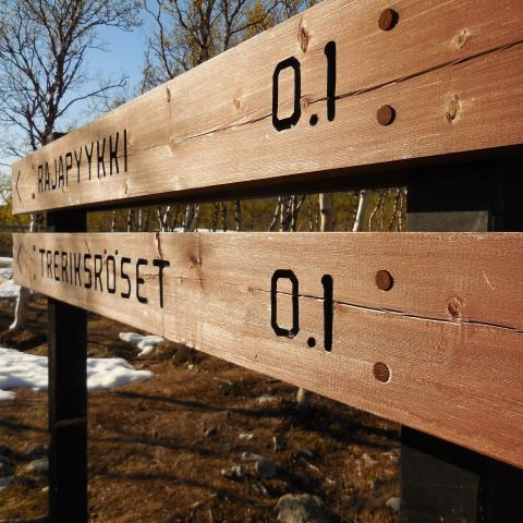 Wooden sign with 0.1 distance to Treriksrøysa