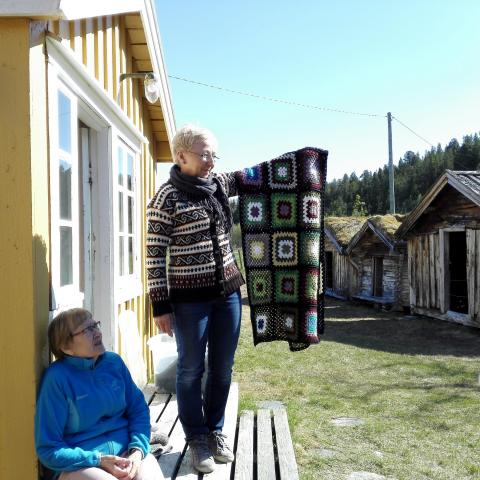 Tørfoss Kven farm in the Reisa Valley in Nordreisa municipality, woman holding a carpet outside the house
