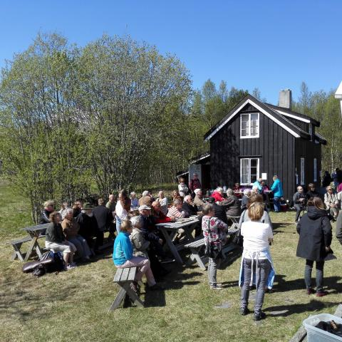 People enjoying a sunny day outside the Kven farm at Tørfoss