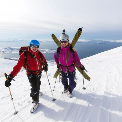 Two skiers on top of Russelvtinden, Lyngen Alps. With a fjord view