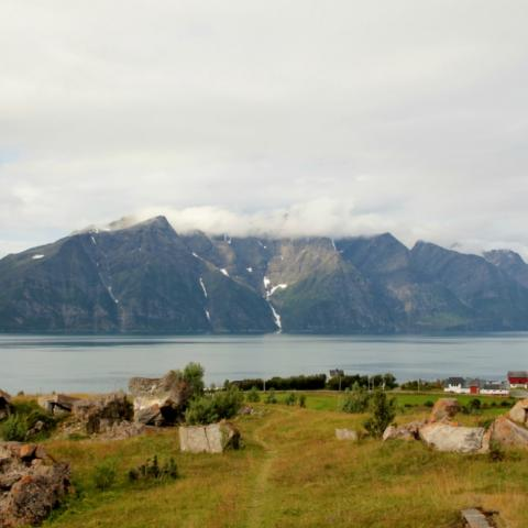 Ruins of a coastal fort, view of the fjord and Lyngen Alps in the background on a cloudy day