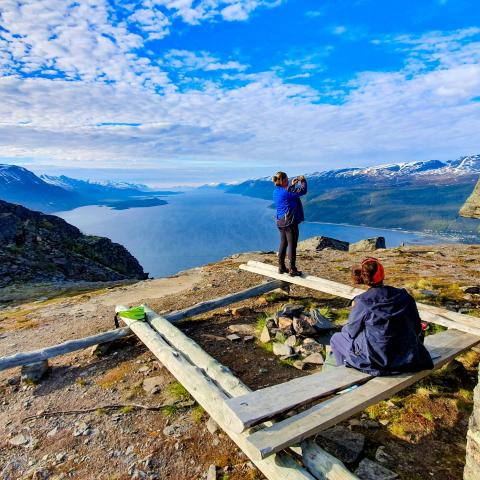 Two persons sitting/standing around a fireplace, enjoying the view of the Lyngenfjord and the LyngenAlps from above
