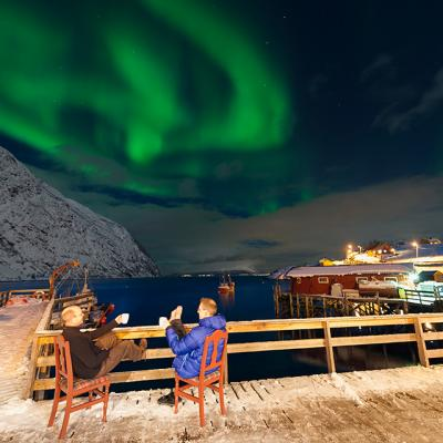 two persons sitting outside on the pier enjoying the northern lights
