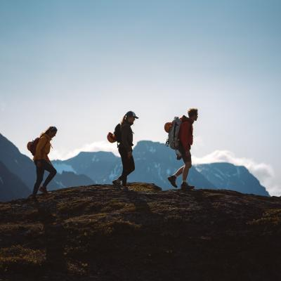 3 persons hiking in the Lyngen Alps, seen as siluettes