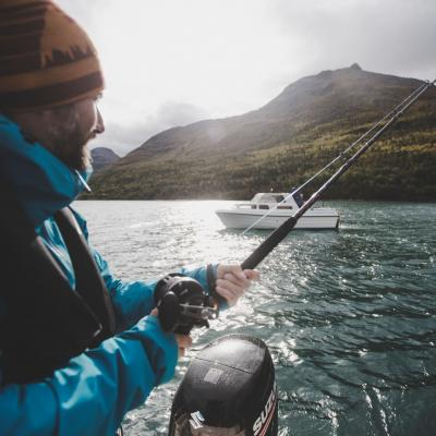 A person fishing on the Lyngenfjord in greyish weather