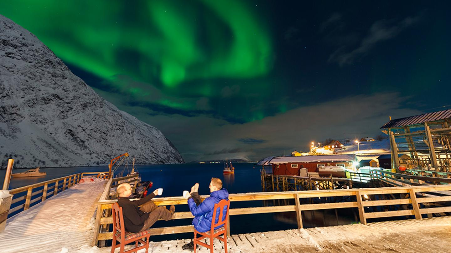 Two guys sitting on the quayside under the northern lights
