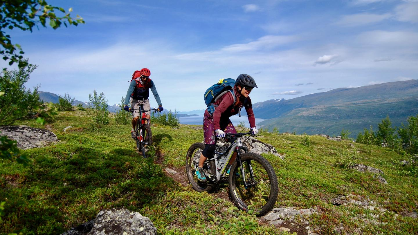 Two mountainbikers on their way from Bollmannsveien, the Lyngenfjord in the background