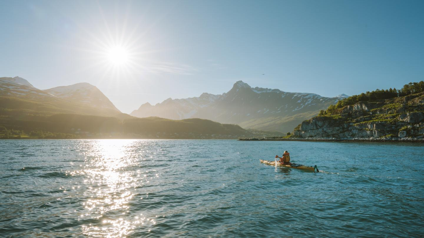 Person in a kayak heading towards the Lyngen Alps and Lyngseidet in the evening sun