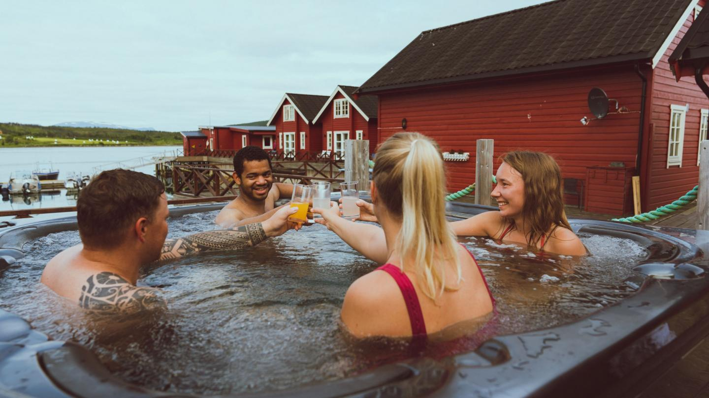 4 persons in a outdoor jacuzzi, red sea side cabins in the background